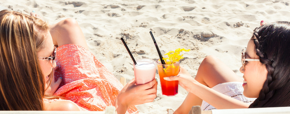 Two girls or woman drinking cocktails in beach club and sitting on sun lounger